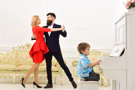 Boy adorable try to play piano musical instrument, while parents dancing. Musician education concept. Child sit next to piano, play music, white interior background. Rich parents enjoy parenthood.