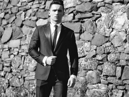 Man young handsome elegant model wears suit white shirt with black skinny necktie looks in camera poses outdoor on masonry background Stock Photo