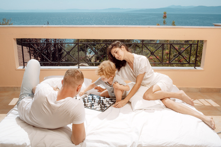 Parents play chess with kid on terrace on sunny day. Smart toddler concept. Family with little son play chess on balcony, nature and sea on background. Dad and mom with child play intellectual game.
