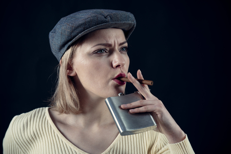 Girl thinking about investigation, holds flask and smoking cigar, copy space. Woman on mysterious face wears kepi, dark background. Blonde lady looks like suspicious detective. Detective concept. Stock fotó