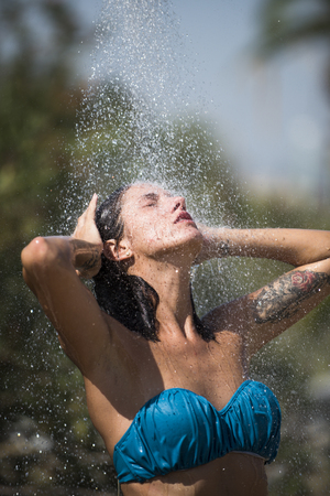 Heat and refreshment concept. Sexy lady in bikini enjoys shower on hot sunny day. Water drops falling on attractive woman. Young beautiful brunette girl taking shower on beach after swimming. Foto de archivo