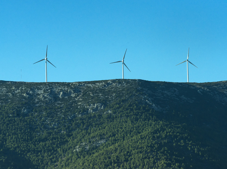 Alternative energy sources concept. Giant white windmills on mountains. Windmills, wind generators on hill, mountain. Landscape with mountains, green forest on sunny day. Imagens