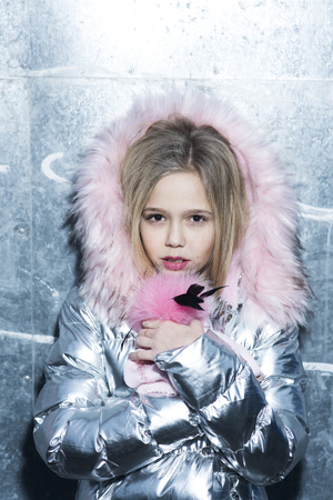Kid fashion trend and style. Girl in winter coat with fur hood, fashion. Little child with long blond hair, hairstyle and beauty. Baby beauty, hair and look. Childhood and youth skincare concept Banque d'images