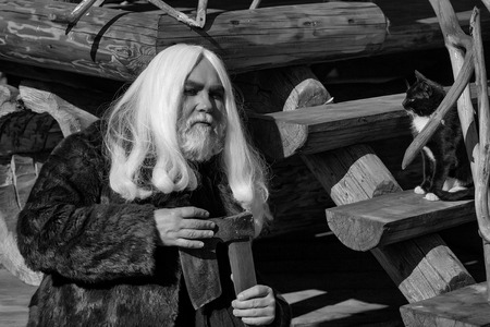 Old man druid with long silver hair and beard in fur coat with axe and cat on steps on log house background