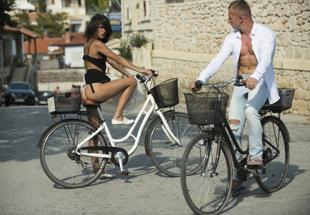Sexy girl with naked buttocks rides bicycle, urban background. Attractive brunette sit on bicycle. Fit and slim girl met handsome man on sunny day travelling by bicycle. Sexy couple concept.