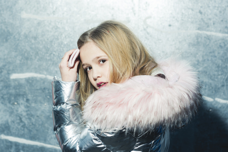 Child in winter coat with fur hood, fashion. Child fashion, trend and style concept.