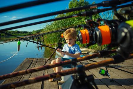 草の川辺でハンサムな若い子供は、釣り竿を保持します。