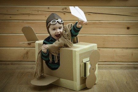 Young child pilot flying a cardboard box on wooden background