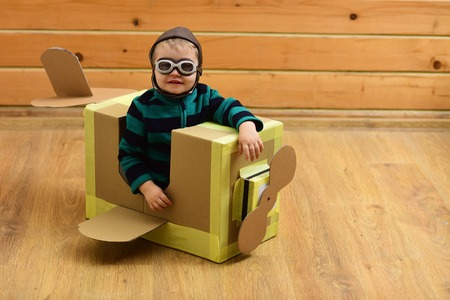 Dream, career, adventure, education. Kid, pilot school, innovation. Pilot travel, airdrome, imagination. Air mail delivery, aircraft construction. Little boy child play in cardboard plane, childhood.