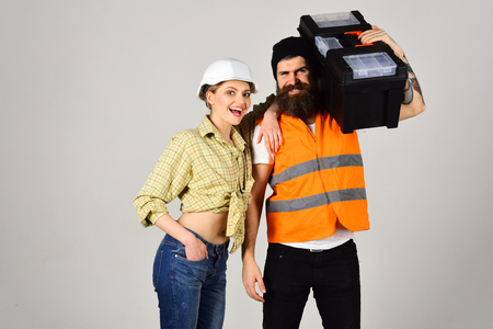 Repairman with girlfriend, copy space. Smiling woman in helmet excited about renovation. Builders with toolbox, couple in love makes repair grey background. Renovation concept. Фото со стока