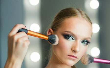 Visage model with makeup brushes. Visage course for glamour makeup.