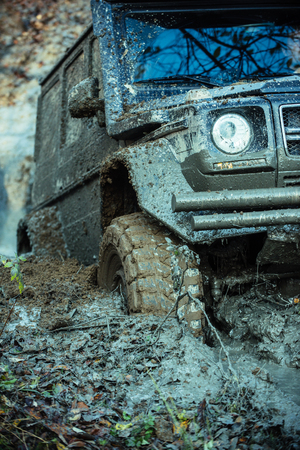 Impassibility of roads concept. Dirty offroad tire covered with mud. Fragment of offroad car stuck in dirt, close up. Wheel in deep rut goes through mud and leaves trail. Stock Photo - 98977764