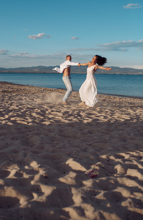 Man and woman dancing, couple happy on vacation. Couple in love running on beach, seashore. Couple in love holds hands, having fun, sea and skyline background. Honeymoon, just married concept.