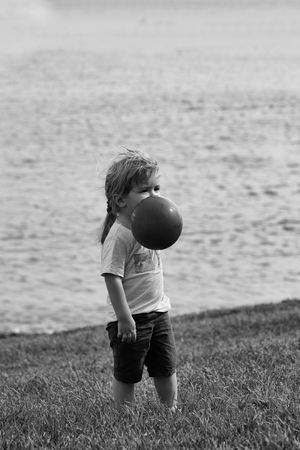 Cute baby boy with blond hair ponytail in blue tshirt and shorts plays with orange toy balloon on green grass by sea on sunny summer day on natural background Stockfoto