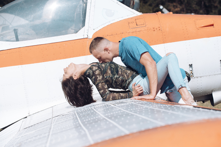 Couple makes love on wing of old plane on sunny day. Couple in love full of desire have sex near airplane on background. Couple on excursion to museum of aviation in open air. Passion concept.