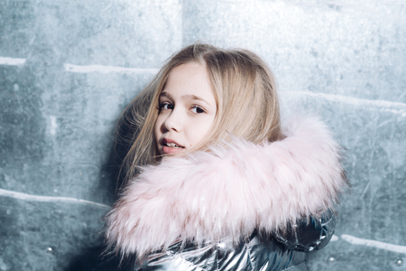 Girl in coat with fur hood, fashion. Girl with long blond hair, hairstyle 免版税图像