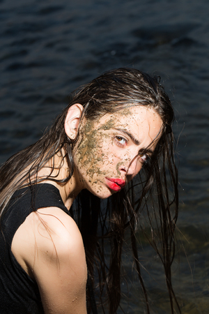 a close up of a womans face covered in mud