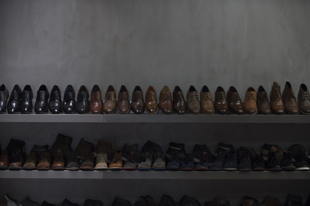 Shelves with brown and black mens shoes. Row of leather mens shoes. Mens shoes, boot sell in store, boutique, shopping mall. Mens shoes concept. Mens fashion, style, quality, leather, leatherette. Stock Photo - 99429419