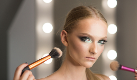 Woman use brushes for makeup, visage. Woman with young face skin in beauty salon. Stock fotó