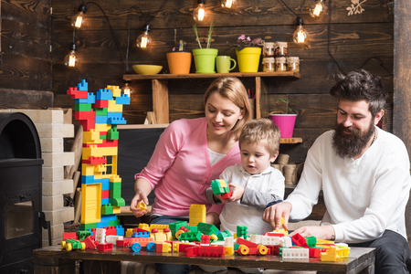 Educational game concept. Father, mother and cute son play with constructor bricks. Kid with parents play with plastic blocks, build construction. Family on busy face spend time together in playroom.