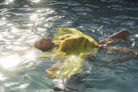 The girl in a yellow dress bathes in pool. Banco de Imagens