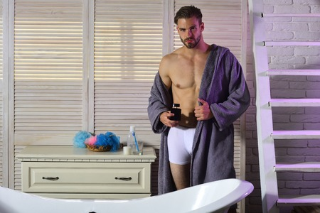 Fashion, home wear, underwear. Sexy man with perfume bottle in bathroom. Grooming, hygiene, health. Macho with muscular torso in underwear and bathrobe at bath. Aroma, fragrance, scent, freshness.