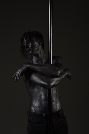 Young strong pole dance man on dark background. Guy with nude torso covered with shimmered sweat or paint hugs pole.