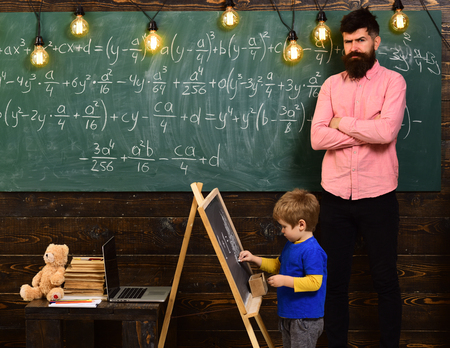 Strict math teacher checking pupil s work. Blond schoolboy solving equation at chalkboard. Preschool education concept.