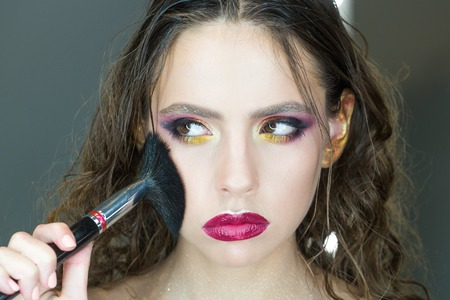 Beauty girl with makeup brush. Bright holiday make up for brunette woman with brown eyes. Beautiful Face and makeover. Perfect skin. Applying makeup
