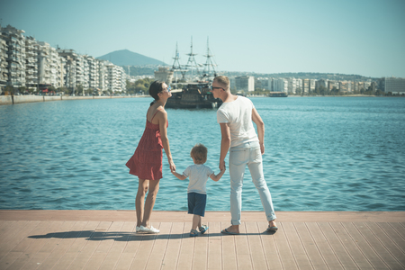 Mother and father going to kiss near their child. Happy family spend time together, holding hands, sea background. Parents with son stand on seafront, rear view. Family vacation concept.