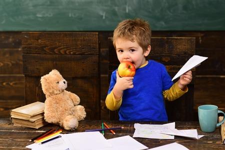 Kid eating juicy apple. Blond boy holding paper plane in his hand. Adorable child in kindergarten.