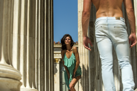 Lady attractives young macho on sunny day. Woman in turquoise dress walking between columns of ancient building. Sexy girl walks with guy, couple in love on vacation. Tourism and honeymoon concept.