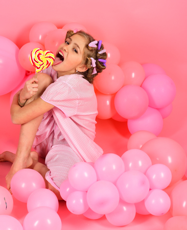Childhood, happiness, sweet dreams. Small girl child eat lollipop on pink. Little girl with candy lollipop. Diet, birthday, punchy pastels, beauty. Party balloons, kid in curlers, pajama fashion.