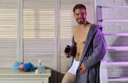 Gay happy smiling with perfume bottle in bathroom. Gay smile with muscular torso in underwear and bathrobe.
