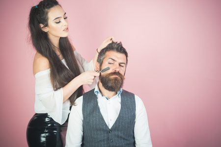 Woman with razor, comb cut hair of man. woman cut beard hair with scissors and comb