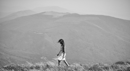 Small beautiful walking brunette girl in white lace summer dress in mountain valley with deep dry spikelet grass sunny windy day outdoor on natural blue background, horizontal picture Banco de Imagens