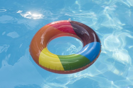 Summer vacation and travel to ocean, Bahamas. Maldives or Miami beach. Relax in spa luxury swimming pool. colorful swim ring or lifebuoy. inflatable ring float in pool blue water. Imagens