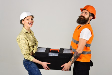 Repairman and girlfriend holding toolbox together, copy space. Renovation concept. Smiling woman in helmet excited about renovation. Builders with toolbox, couple in love makes repair grey background.