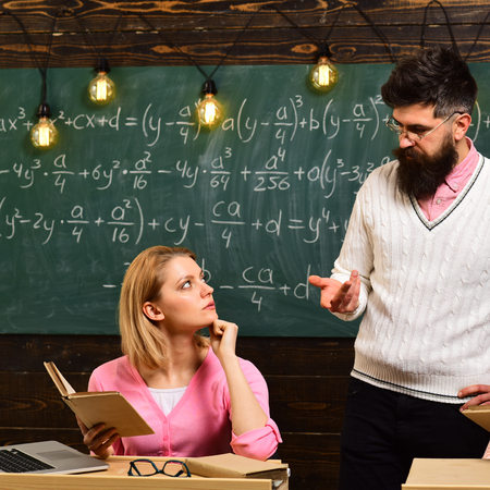 College and education concept. Girl student listening bearded teacher, lecturer, professor. Student, young scientist studying, holds book , while professor teaches, explains, chalkboard background. Stock fotó