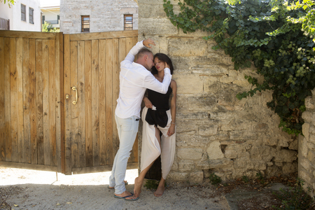 Sensual couple hiding out of sun with ancient rocky wall and old fence on background. Couple in love hugs in shadow on hot sunny summer day. Man and woman full of desire. Hot and desire concept.