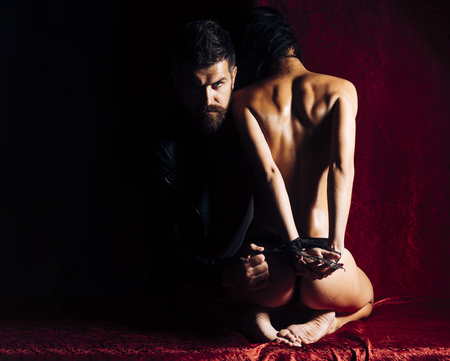 Dominance and submission, couple. Erotic games, sex, orgasm, girl and man. Sexy woman with tied hands, buttocks. Couple in love, bdsm, bearded man and naked girl. Love, man and woman with tied hand. Фото со стока
