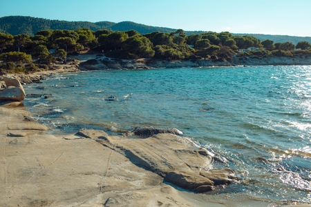 Rocky beach washed by waves, sea and green tropical forest on background. Rocky beach of sea, clear, transparent water near big stone, rock. Nature landscape on sunny summer day. Nature concept.