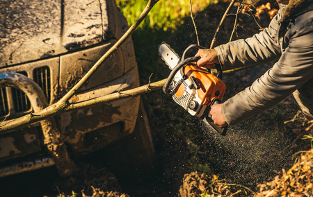 Male hands hold chainsaw and car covered with mud on sunny nature background. Sawing branch in front of bumper and light of SUV. Impassibility of roads concept.