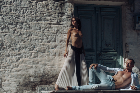 Woman with naked breasts, man with nude torso lies outdoor. Sexy couple undressing under sunlight with ancient rocky wall and old door on background. Couple enjoys nudity. Passion and erotic concept.