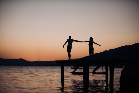 Couple in love on romantic date in evening at dock, copy space. Romance and love concept. Silhouette of sensual couple dancing on pier with sunset above sea surface on background. Stock Photo