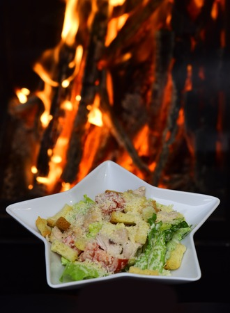 Caesar salad served in white plate in shape of star. Traditional dish in the restaurant - Caesar salad, fire on background. Restaurant dish concept.