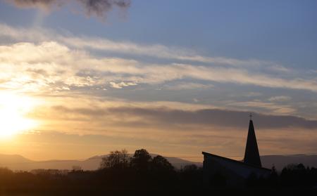 Landscape and church, cross silhouette on cloudy sunset sky. Sundown, cloudscape, nature, environment. Religion, faith, believe.