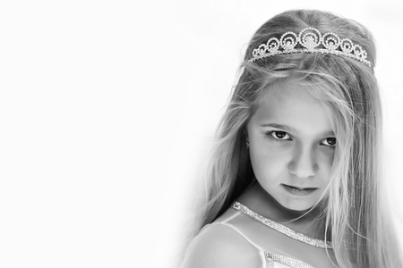 small girl kid with long blonde hair and pretty face in dress and prom princess crown standing on white background, closeup Stock Photo