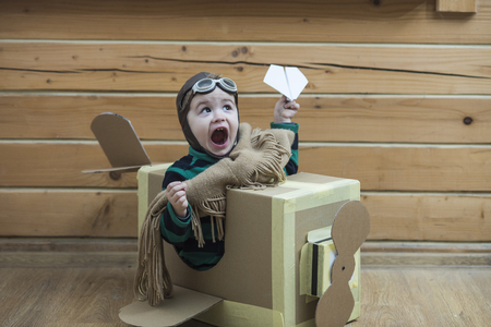Little boy playing with cardboard airplane on wooden wall background