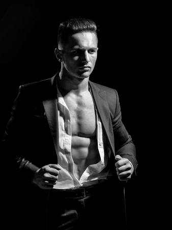 young handsome gentleman wearing fashion black suit in white open shirt with bare torso Фото со стока